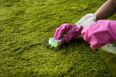close-up partial view of person in rubber gloves cleaning carpet with rag and detergent spray