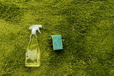 top view of spray bottle with detergent and rag on green carpet with copy space