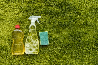 top view of bottles with detergent and rag on green carpet with copy space
