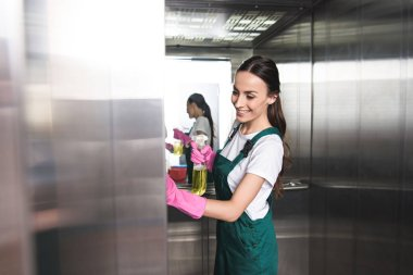 beautiful smiling young janitor cleaning elevator with detergent and rag