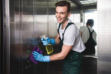 young cleaning company worker cleaning elevator and smiling at camera