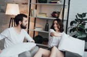 beautiful young couple in pajamas having pillow fight at home