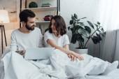 krásný mladý pár v pyžamu ležel v posteli, pomocí přenosného počítače a při pohledu na sebe