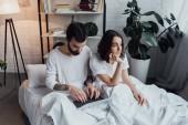 Fényképek ember az ágyban fekve, és használ laptop míg unatkozik nő propping állát, és keres el a hálószobában