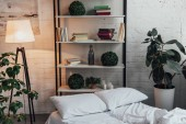Fotografie modern interior design of bedroom with rack, plants, lamp, bed and brick wall