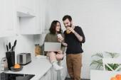 Mann trinkt Saft und benutzt Smartphone, während lächelnde Frau während des Frühstücks in der Küche Laptop benutzt