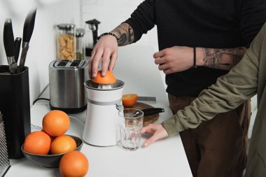 partial view of couple preparing orange juice during breakfast in kitchen