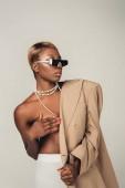 Fotografie nackte afrikanische amerikanische Frau posiert in Sonnenbrille und beige Jacke isoliert auf grau