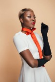 stylish african american girl posing in white dress, trendy scarf and black gloves isolated on beige