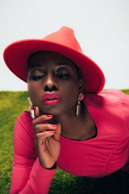 beautiful stylish african american woman in pink dress and hat posing on green grass