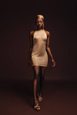 attractive african american woman with short hair posing in glamorous dress on brown
