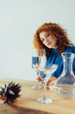 Attractive stylish redhead woman posing near table with glasses of water isolated on grey stock vector