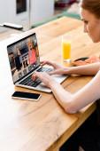 Žena pomocí notebooku s on-line rezervace webové stránky v blízkosti smartphone, pomerančový džus a toasty na stole