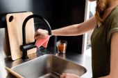 Fotografie Cropped view of woman holding knife and rag near kitchen sink