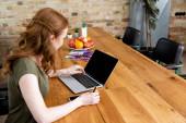 Oldalnézet a szabadúszó használja laptop, miközben a hitelkártya az asztalnál