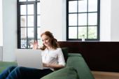 Selektivní zaměření usměvavé ženy s videohovory na notebooku doma