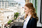 Side view of positive woman looking at urban street on balcony