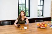 Červené vlasy žena jíst croissant drží šálek kávy doma