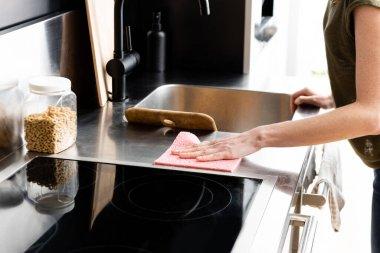 Mutfak atölyesini paçavrayla temizleyen kadın manzarası.