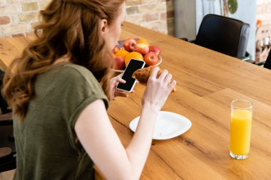 Selective focus of woman using smartphone while holding croissant near glass of orange juice on table stock vector