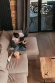 felső kilátás lány ül a kanapén közel popcorn vödör és aranyos francia bulldog