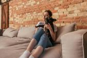 boldog lány gazdaság karok aranyos francia bulldog, miközben ül a kanapén közelében smartphone
