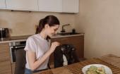 glückliche junge Frau mit aufgeschnittener Avocado und Blick auf französische Bulldogge