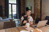 vidám szabadúszó gazdaság karok aranyos francia bulldog és nézi kamera közelében laptop