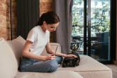 vonzó szabadúszó megérintése fekete francia bulldog közelében laptop a nappaliban