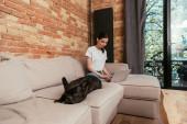 krásný freelancer pomocí notebooku v blízkosti francouzského buldoka v obývacím pokoji