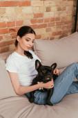fiatal nő ül kanapén fekete francia bulldog