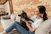 boldog nő ül a kanapén, és megérinti aranyos francia bulldog