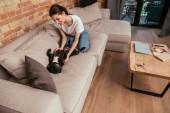 vidám lány játszik aranyos francia bulldog kanapén a modern nappaliban