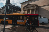 KODAŇ, DÁNSKO - 30. dubna 2020: Žena na kole v blízkosti autobusů na městské ulici