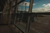 Sklo okna s fasádou letištní budovy s zataženou oblohou na pozadí
