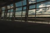 Letištní okna s oblačným nebem a letištěm v pozadí v Kodani, Dánsko
