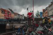COPENHAGEN, DÁNIA - Április 30, 2020: Kerékpárok közelében csatorna Nyhavn kikötő felhős ég a háttérben