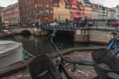 Selective focus of bicycles on promenade near canal on Nyhavn Harbor, Copenhagen, Denmark