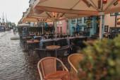 Selektiver Fokus von Tischen und Stühlen unter Sonnenschirmen auf der städtischen Straße, Kopenhagen, Dänemark