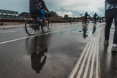 Selective focus of people walking and riding bicycles on urban street during rain in Copenhagen, Denmark