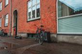 Photo Bikes and scooter near brick facade of building on urban street in Copenhagen, Denmark