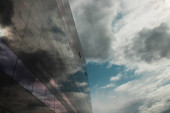 COPENHAGEN, DENMARK - APRIL 30, 2020: Low angle view of glass facade of Black Diamond Royal Library with cloudy sky at background, Copenhagen, Denmark