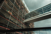 Low angle view of building construction with glass corridor and cloudy sky at background in Copenhagen, Denmark