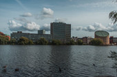 Selective focus of ducks on river with buildings and cloudy sky at background, Copenhagen, Denmark