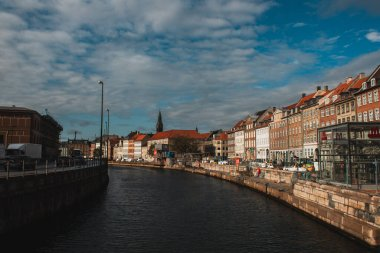 COPENHAGEN, DENMARK - APRIL 30, 2020: Canal with buildings on promenade and cloudy sky at background