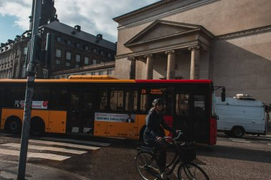 COPENHAGEN, DENMARK - APRIL 30, 2020: Woman riding bicycle near buses on urban street stock vector