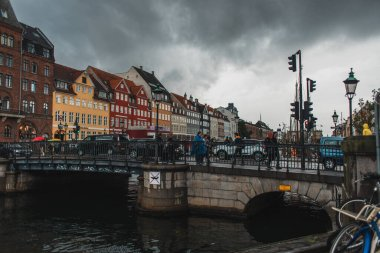 COPENHAGEN, DENMARK - APRIL 30, 2020: People walking on bridge near canal with Nyhavn urban street and cloudy sky at background stock vector