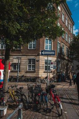 COPENHAGEN, DENMARK - APRIL 30, 2020: Selective focus of bicycles near pointer on urban street stock vector