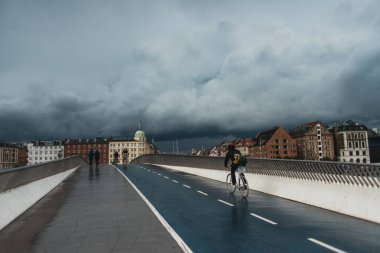 COPENHAGEN, DENMARK - APRIL 30, 2020: People walking on bridge with urban street and cloudy sky at background
