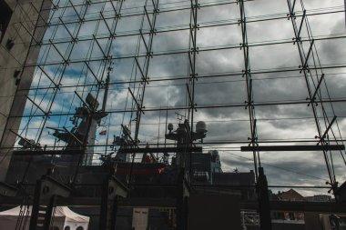 COPENHAGEN, DENMARK - APRIL 30, 2020: Ship in harbor near facade of Royal danish library with cloudy sky at background stock vector